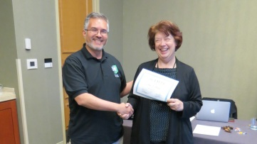 HAMTE President Enrique Galindo thanks outgoing HAMTE Treasurer Sue Mau for her service.
