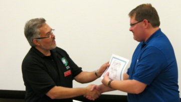 HAMTE President Enrique Galindo thanks outgoing Newsletter Editor Travis Miller for his service.